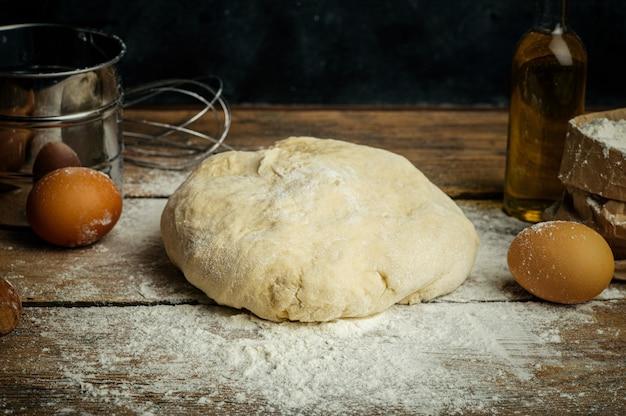 Pizzadeeg het koken in de huiskeuken. zelfgemaakt deeg voor brood, pizza, gebak en broodjes. deeg ingrediënten op een houten rustieke achtergrond
