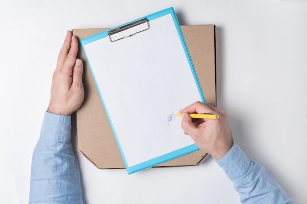 Pizzadoos en mannenhand zet een handtekening op het document. voedsel levering aan huis concept.