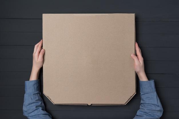 Pizzadoos in kinderhanden. zwarte muur. bovenaanzicht. kopieer ruimte.