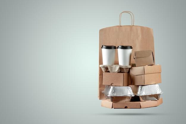 Pizzadozen en papieren zak met een wegwerp kopje koffie en een wokdoos op een blauwe achtergrond