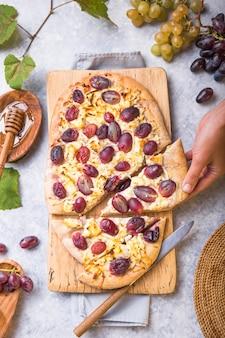 Pizzakorst met geitenkaas en rode druiven. vegetarisch, graanvrij, koolhydraatarm, glutenvrij dieetconcept
