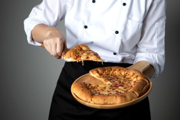 Pizzapan in chef-kokhand met traditioneel traditionele de stijl van het kaas stretchitalian voedsel