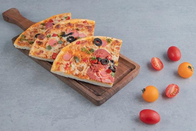 Pizzaplakken op een dienblad naast kleine tomaten op marmer