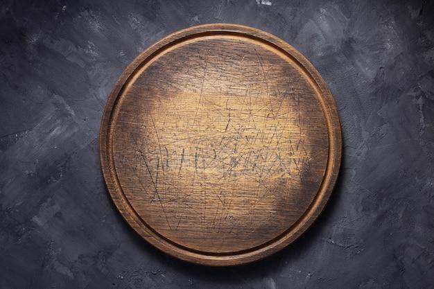 Pizzasnijplank aan tafel of muur, met stenen achtergrondstructuur