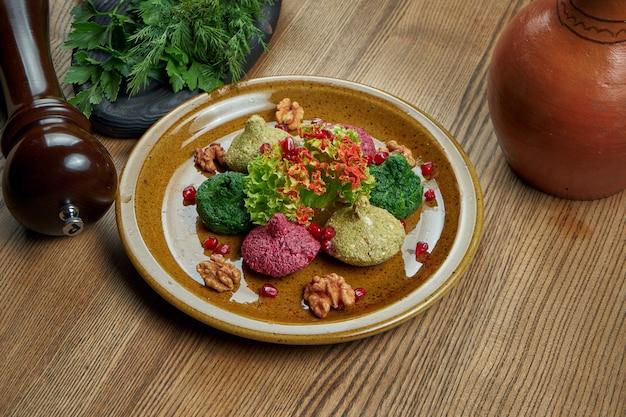 Pkhali in keramische plaat. kopieer ruimte. traditioneel georgisch voorgerecht pkhali gemaakt van gehakte en gehakte kool, aubergine, spinazie, bonen, bieten en gecombineerd met walnoten, knoflook en kruiden