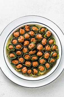 Pkhali. veganistisch voorgerecht uit de georgische keuken. een zachte mix van gegrilde paprika en walnoten met pittige kruiden, gewikkeld in gegrilde courgette bladeren. gezonde keuken.