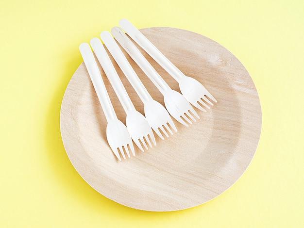 Plaat en vijf vorken op geel papier achtergrond. houten biologisch afbreekbare schalen. milieuvriendelijke keuze en natuurvriendelijk. het concept van een wereld zonder plastic en een schone planeet. ecologie, geen afval.