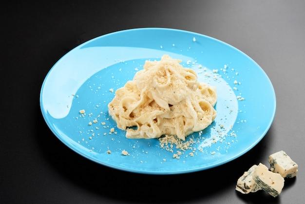 Plaat italiaanse penne pasta gegarneerd formaggio romige zoute saus en basilicum geserveerd blauwe schotel