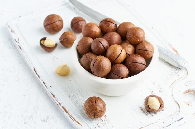 Plaat met amandelen in endocarp, hele en gehakte open noten in bulk op snijplank