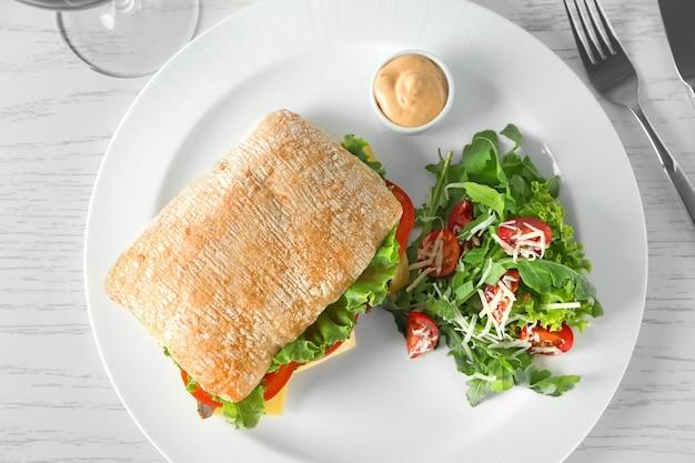 Plaat met biefstuksandwich en groentesalade op lijst