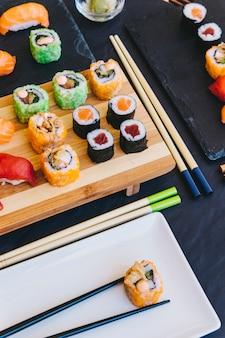 Plaat met broodje dichtbij sushi