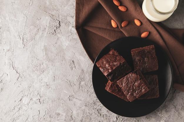 Plaat met chocoladetaart segmenten, amandel en fles melk op grijs, bovenaanzicht