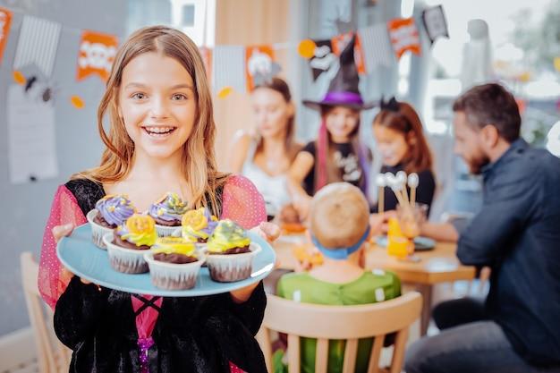Plaat met cupcakes. stralend donkerogig schoolmeisje dat halloween-de plaat van de kledingsholding met lekkere heldere cupcakes draagt