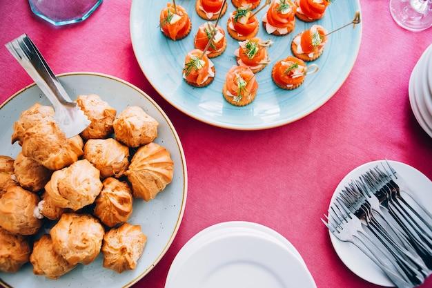 Plaat met eclairs op de tafel. plaat op een roze tafellaken. canapé met rode vis. witte borden, vorken, wijnglazen. uitzicht van boven