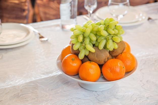 Plaat met fruit sinaasappels, druiven, kiwi met lege glazen en bestek op de