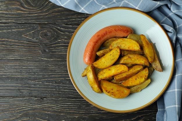 Plaat met gebakken aardappel en worst, en keukenhanddoek op houten achtergrond