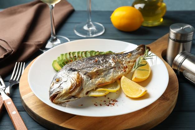 Plaat met gebakken dorado-vissen op houten versierd