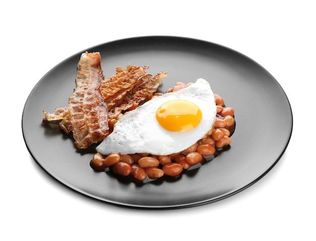 Plaat met gebakken ei, spek en bonen op een witte ondergrond