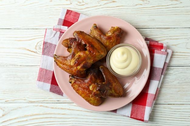 Plaat met gebakken kippenvleugels en saus op keukendoek op houten