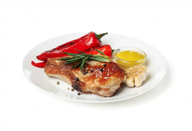 Plaat met gebakken lapjes vlees en groenten die op witte achtergrond worden geïsoleerd