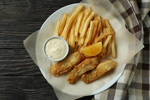 Plaat met gebakken vis en patat op houten met keukendoek
