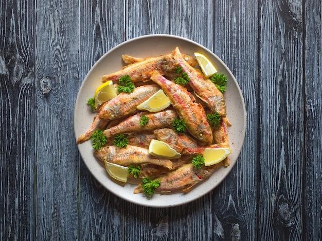 Plaat met gebakken vis op een houten achtergrond