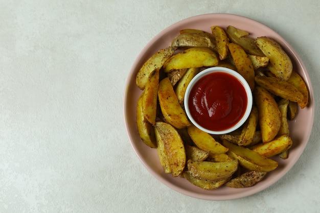 Plaat met gebraden aardappel en saus op geweven wit