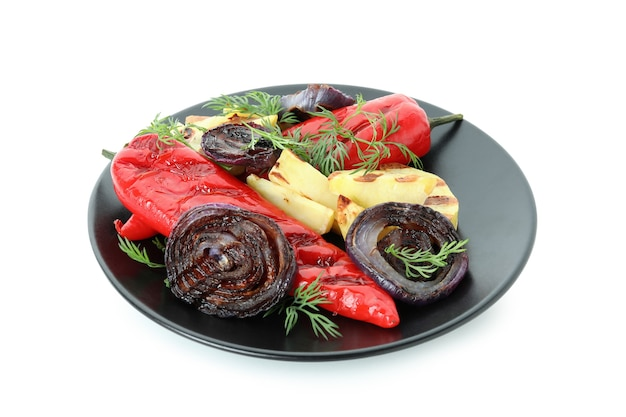Plaat met gegrilde groenten op wit wordt geïsoleerd