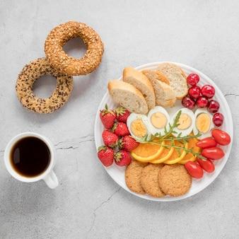 Plaat met gekookt ei fruit en groenten en kopje koffie