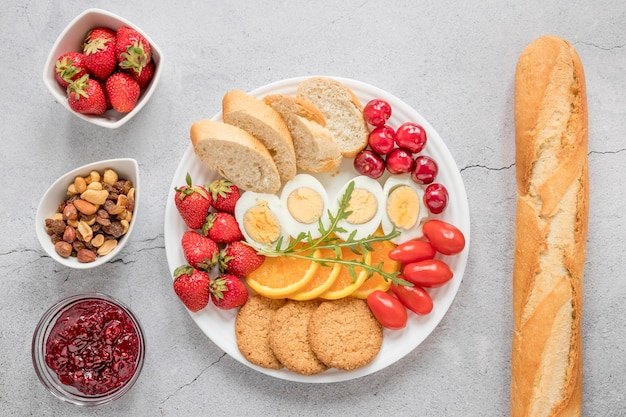 Plaat met gekookt ei fruit en groenten voor het ontbijt