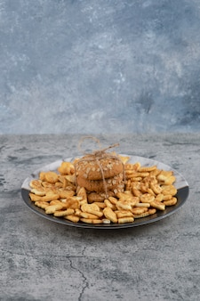 Plaat met gezouten crackers en havermoutkoekjes op marmeren achtergrond.