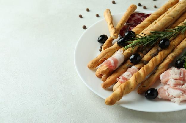 Plaat met grissini en snacks op wit gestructureerd oppervlak