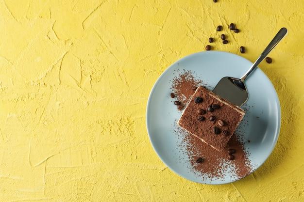 Plaat met heerlijke tiramisu op gele achtergrond. lekker dessert