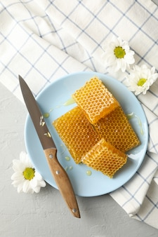 Plaat met honingraten en mes op witte achtergrond
