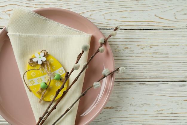 Plaat met houten paasei, keukenservet en katjes op houten achtergrond