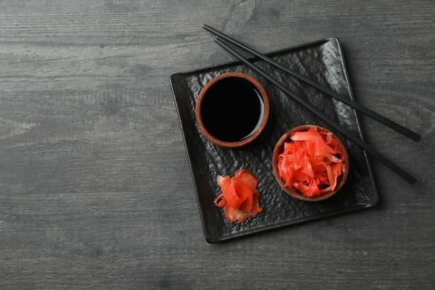 Plaat met ingelegde gember, sojasaus en eetstokjes op donkere houten oppervlakte