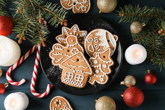 Plaat met kerstkoekjes, kerstboom en speelgoed op blauw, bovenaanzicht. detailopname