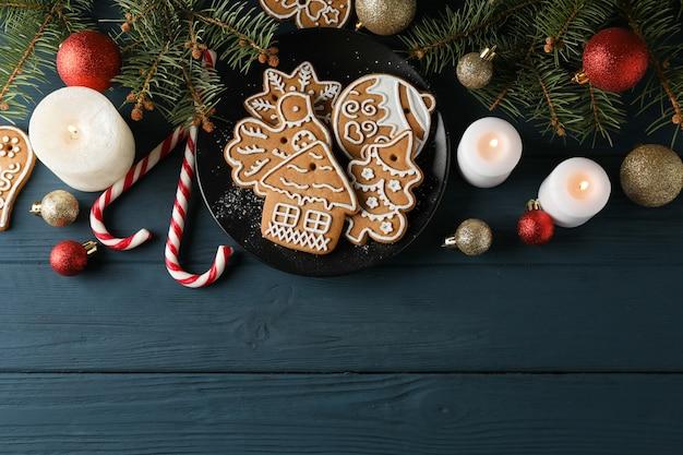 Plaat met kerstkoekjes, kerstboom en speelgoed op blauw, ruimte voor tekst. bovenaanzicht