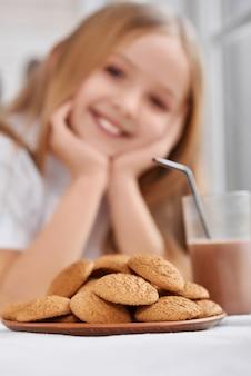 Plaat met koekjes en chocolademelkglas dichtbij meisje