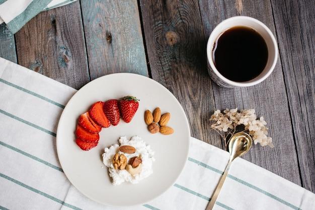 Plaat met kwark, aardbeien en noten, een kopje koffie en handdoeken op houten tafel, gezonde voeding, ontbijt