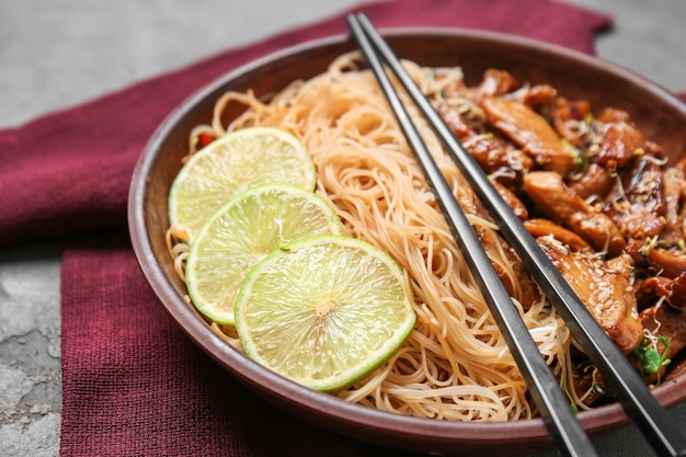 Plaat met lekkere chinese noedels en vlees op tafel, close-up