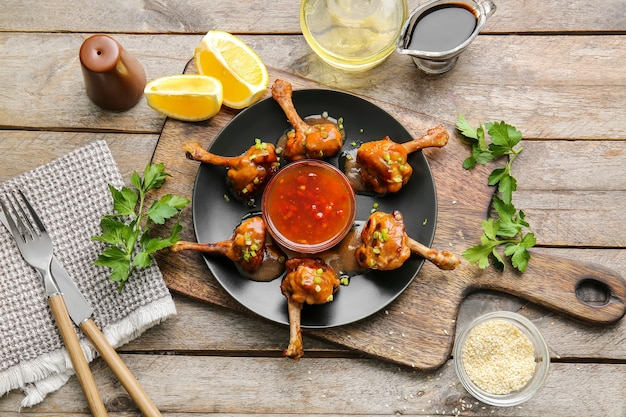 Plaat met lekkere kip lollies en saus op houten oppervlak