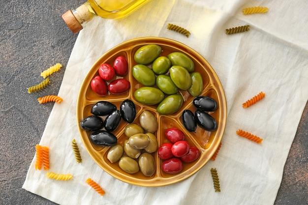 Plaat met lekkere olijven op grijze tafel
