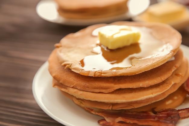 Plaat met lekkere pannenkoeken en spek op houten tafel