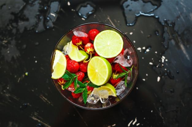 Plaat met limoen, aardbei en ijs klaar om te worden opgeslagen in de blender