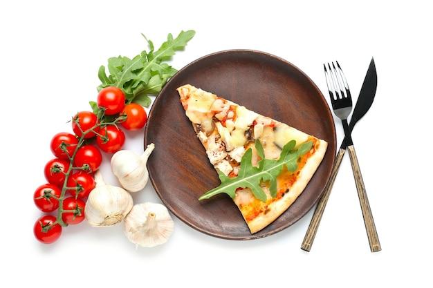 Plaat met plak van smakelijke pizza op witte ondergrond