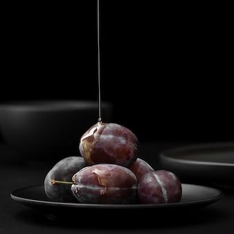 Plaat met pruimen en honing op een donkere achtergrond
