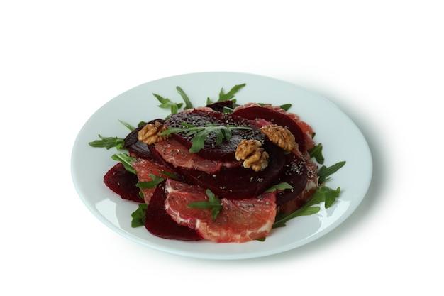 Plaat met smakelijke bietensalade die op witte lijst wordt geïsoleerd