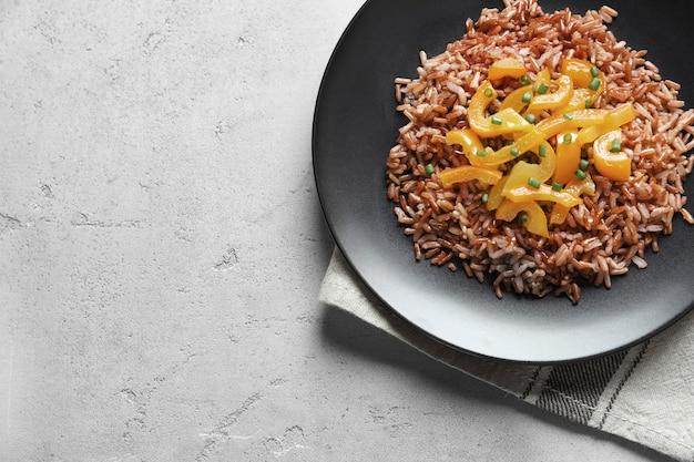 Plaat met smakelijke bruine rijst en groenten op tafel