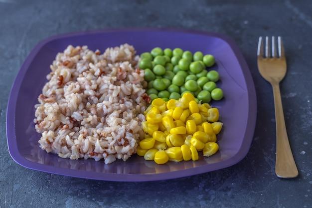 Plaat met smakelijke bruine rijst en groenten
